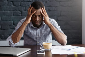 Frustrated young African-American businessman having bad headache, squeezing his temples, feeling stressed at work, sitting at desk with generic laptop computer, documents, mug and mobile phone