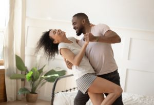 A newlywed couple dance around their bedroom, enjoying the peace of mind that a strong life insurance policy can give you and your spouse.